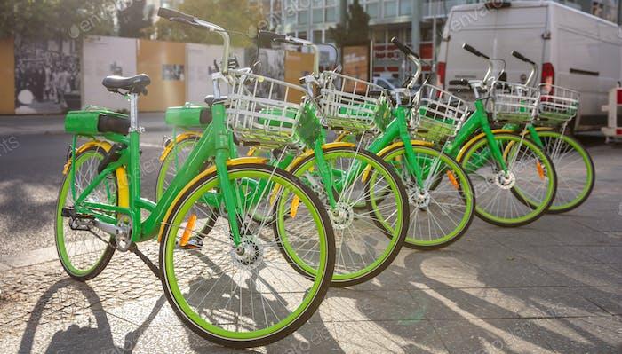 Alquiler de bicicletas con cestas estacionadas en una calle adoquinada, Berlín, Alemania