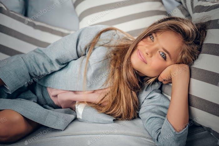 Teenage girl lying on sofa in a living room.