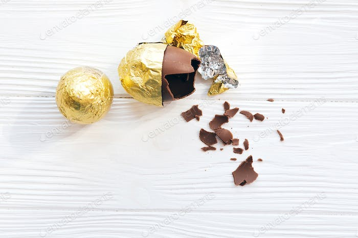 Stylish Easter egg in golden foil and broken chocolate egg with chocolate pieces