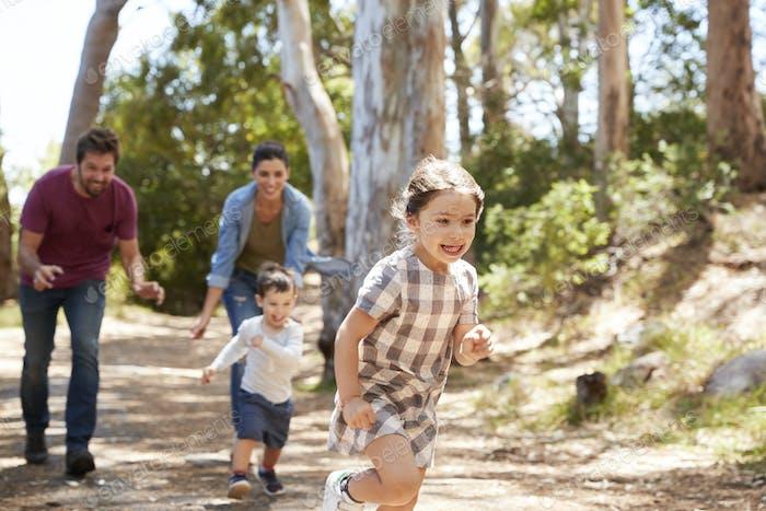 Familie entlang Weg durch Wald zusammen laufen