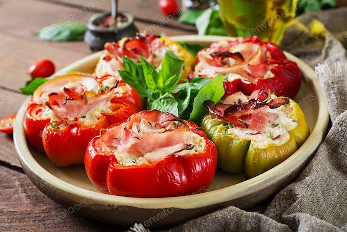 Gefüllte Paprika mit Hüttenkäse und Speck in Platte auf dem Holztisch. Balkan-Essen.