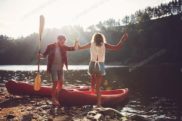 Paar gehen für eine Kanufahrt in den See.