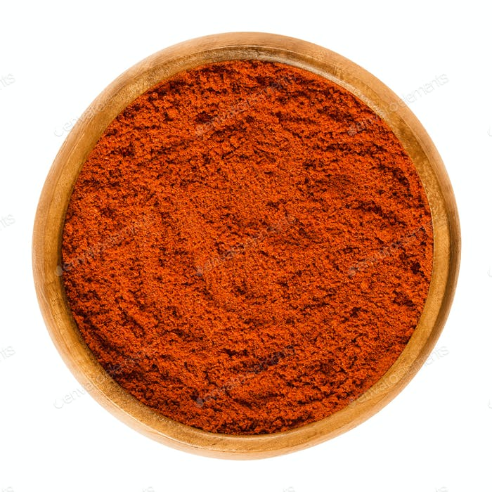 Sweet pepper red paprika powder in wooden bowl over white