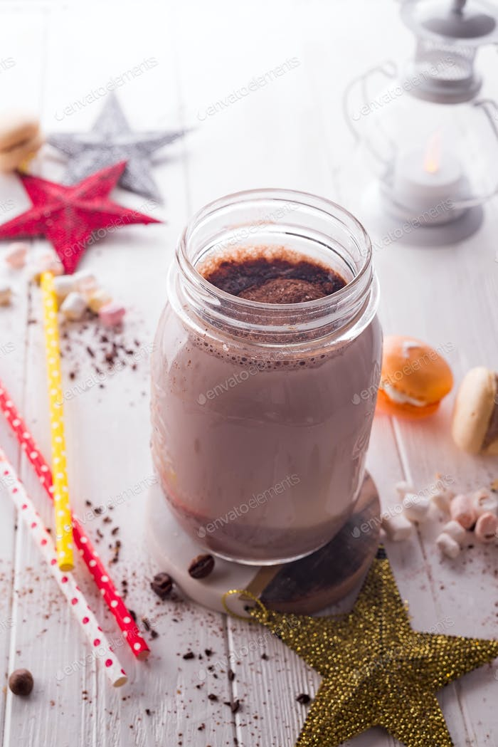 Cocoa with marshmallow and straws in the glass jar decorated with christmas stars