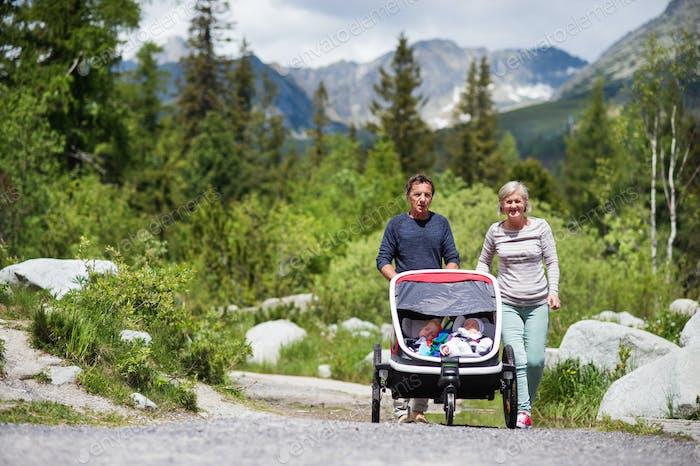 Senior couple and children in jogging stroller, summer day.