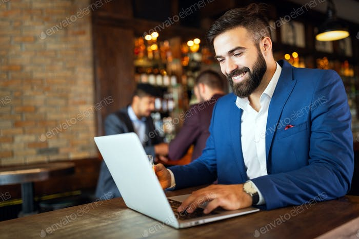 Portrait of a successful business man sitting at the cafe working on a laptop