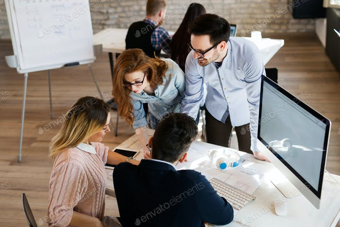 Group of young perspective architects discussing in office