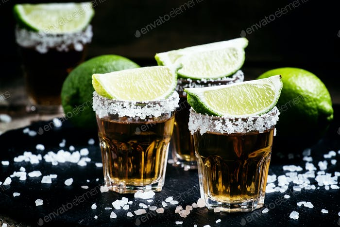 Mexican tequila in a glass, sprinkle with salt with slices of lime