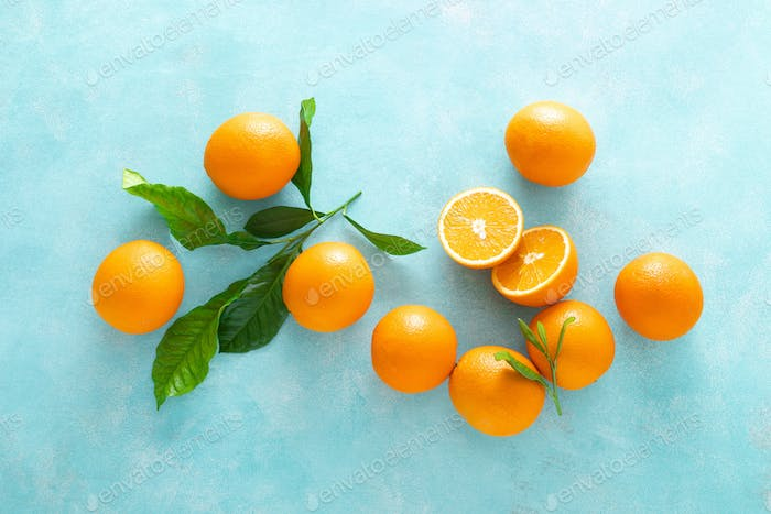 Orange freshly squeezed juice in glass and fresh fruits on a blue vivid background, top view
