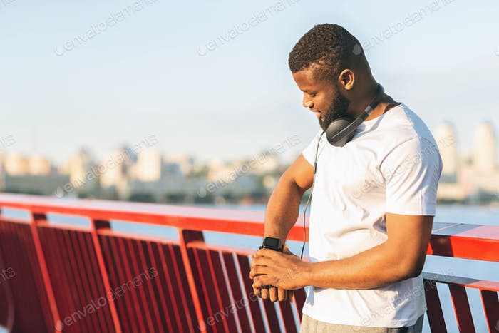 Athletic black guy looking at his smartwatch