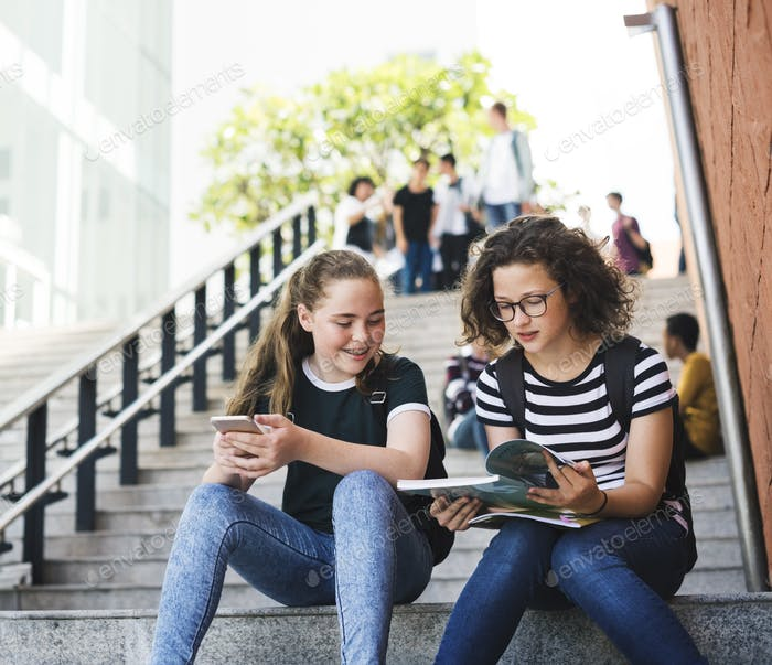 Group of students sitting on staircase using lptop