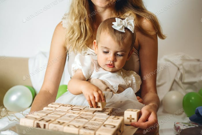 Little girl playing with wooden ABC blocks. Plastic-free wooden zero waste kids toys for safe and