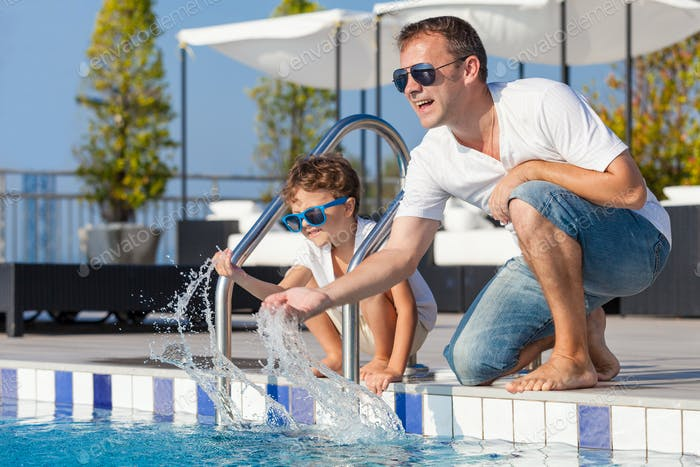 Father and son relaxing near a swimming pool  at the day time.