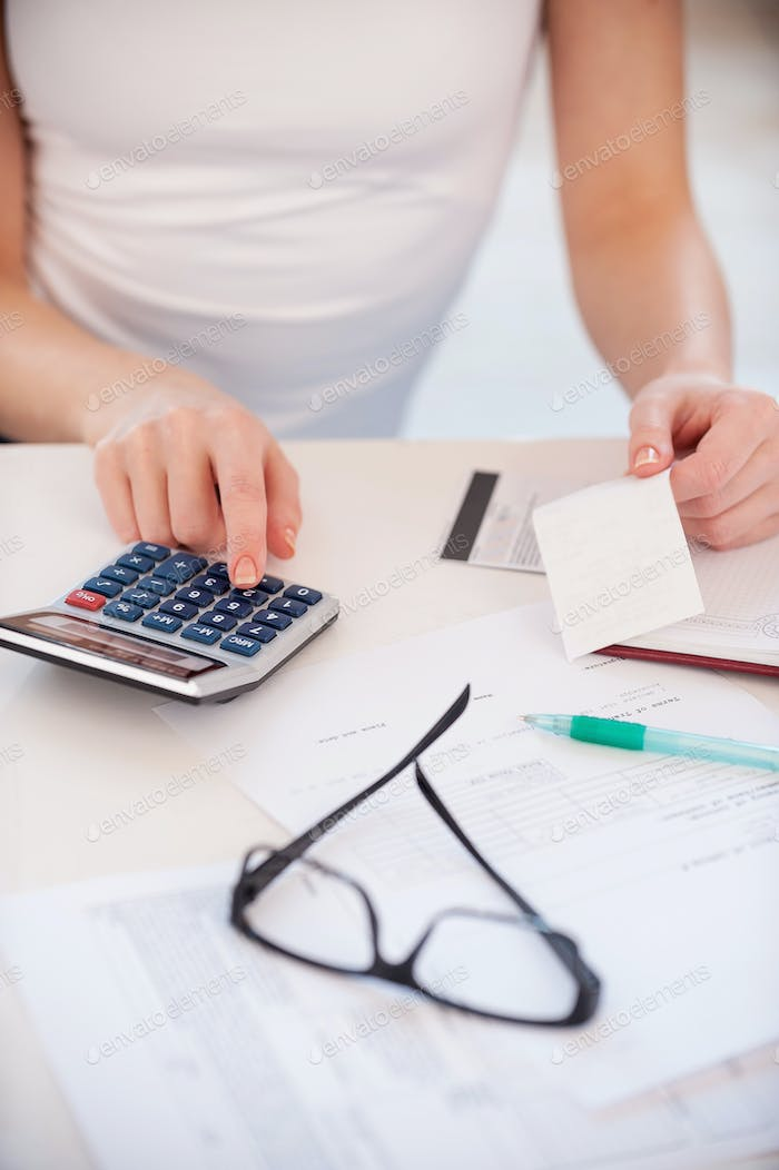 Calculating her expenses. Cropped image of woman calculating her expenses while holding a bill
