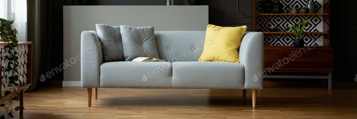 Grey sofa with yellow cushion and open book in real photo of dar