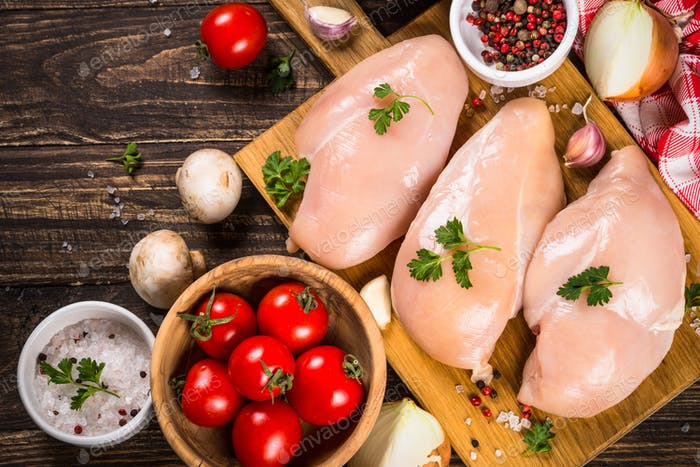 Chicken fillet with ingredients for cooking on wooden table