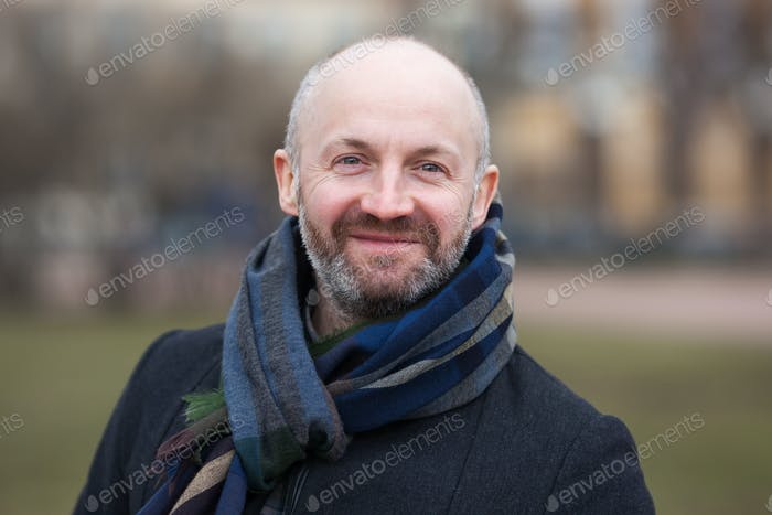 A middle-aged man in a scarf and jacket for a walk around the city.