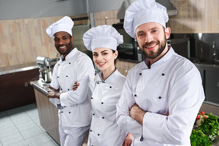 Multiracial team of cooks looking at camera by cooking table