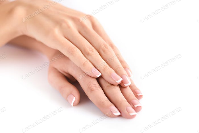 Beautiful woman hands with french manicure on a white background