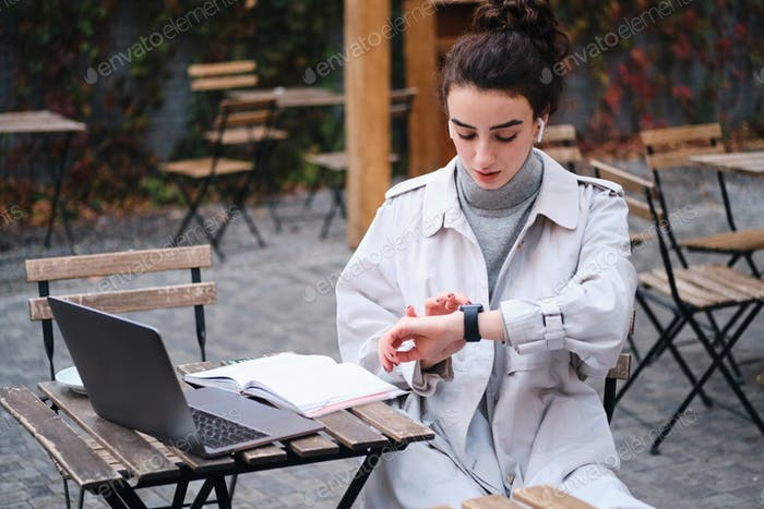 Attractive brunette girl in trench coat confidently using smartwatch studying in cafe on city street