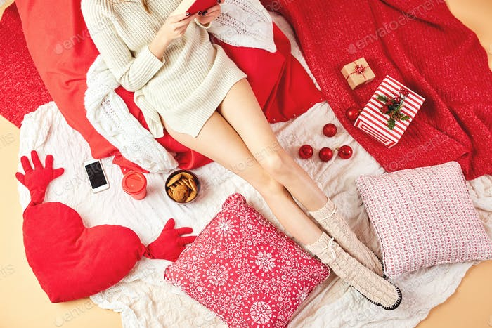 Girl dressed knitted dress and knitted socks lies and reads a book on red-white blankets and pillows