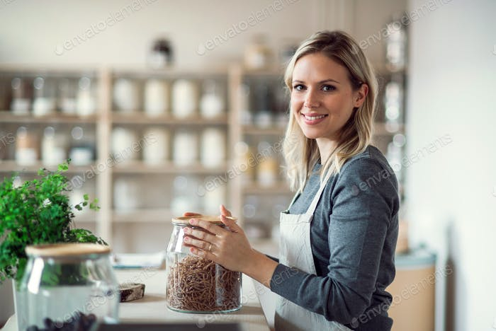 A female shop assistant in a zero waste shop, holding a jar with groceries.
