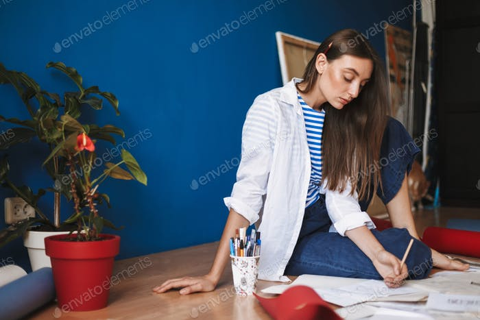 Young painter in white shirt and striped T-shirt sitting on floo