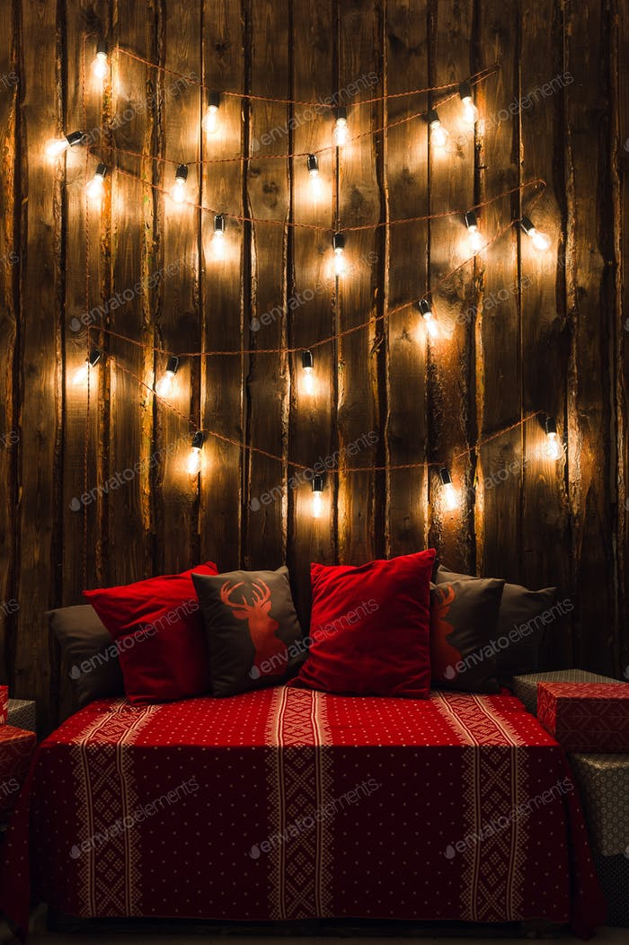 Wooden room in rustic house with wooden wall and designer light bulbs, decorated place for seat. Red