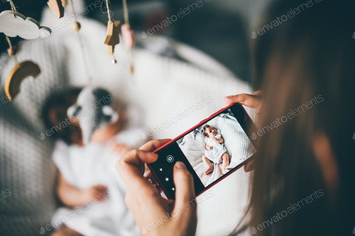 Mother taking a picture of A baby with a mobile phone.
