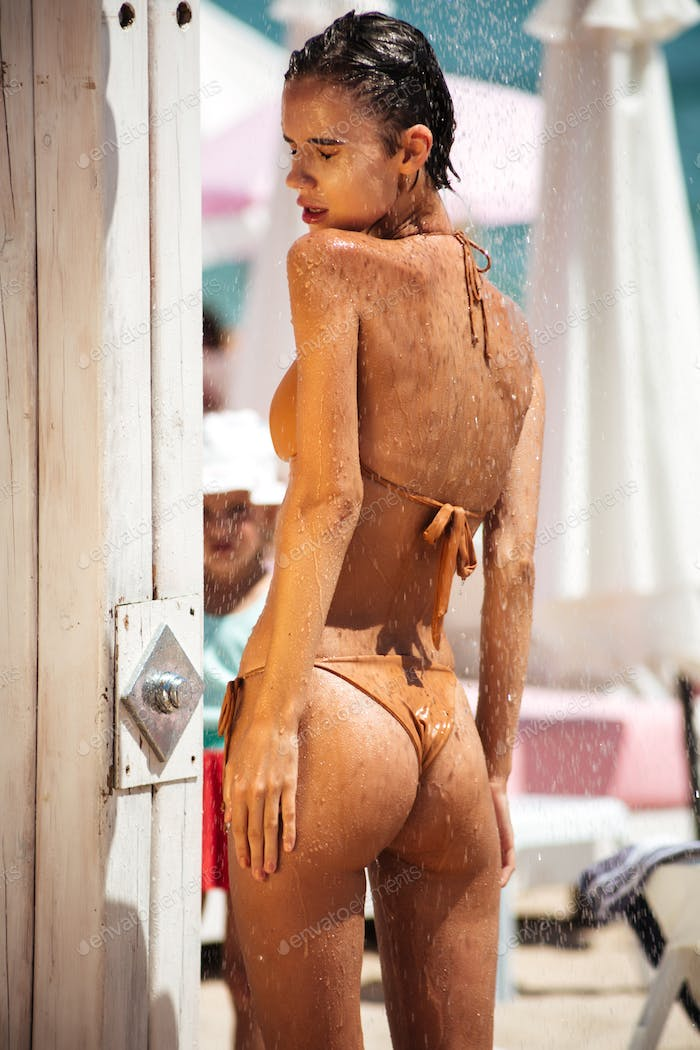 Portrait of young beautiful girl in swimsuit taking shower while spending time on the beach