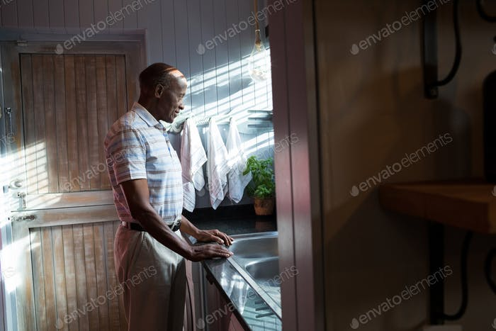Side view of thoughtful man standing by sink