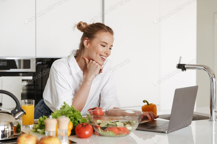 Happy young pretty woman using laptop computer cooking.