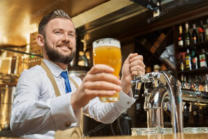 Handsome barman holding cold lager beer glass
