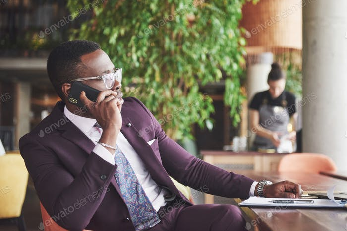 Portrait of a young and handsome African American businessman talking in a suit over the phone
