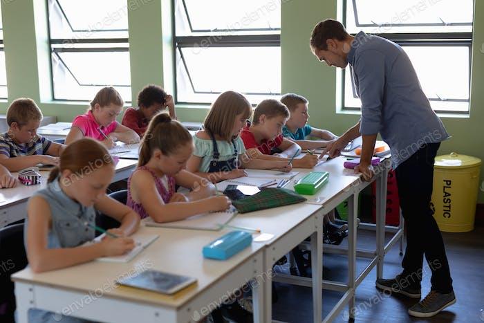 Gruppe von Schulkindern sitzen an Schreibtischen in einem Grundschulunterricht