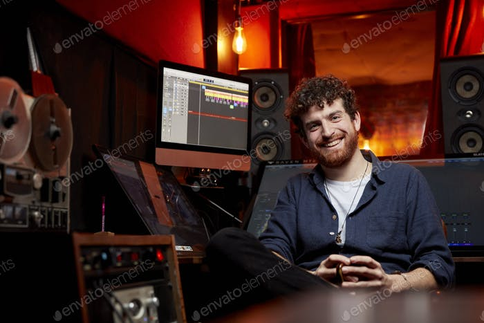 Portrait of man smiling to camera sitting in music studio holding cup of coffee