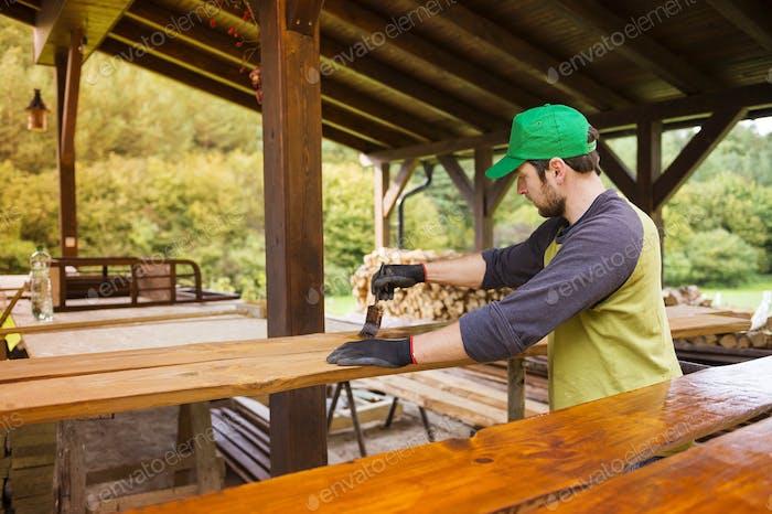 Handyman varnishing wooden planks outside
