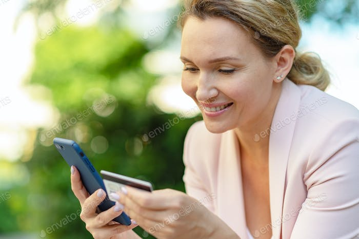 Businesswoman with a credit card and phone makes purchasing outdoors.