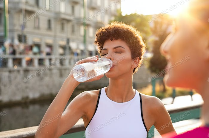 Athletic woman drinking water after workout