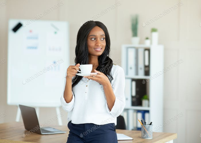 Portrait of charming black female manager in formal wear drinking coffee at contemporary office