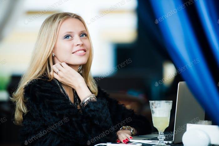Young gorgeous European woman with pretty face thinking about something while sitting with laptop