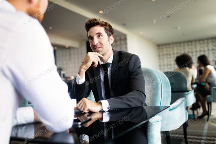 Image of young businessman with cup of coffee communicating with colleague