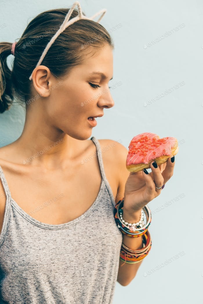 Sexy brunette lady eat sweet heart shaped donut.