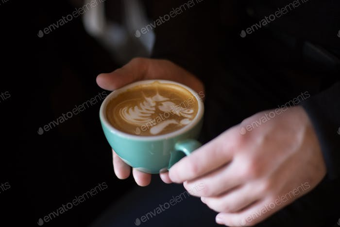 Hand holds cup with coffee and latteart