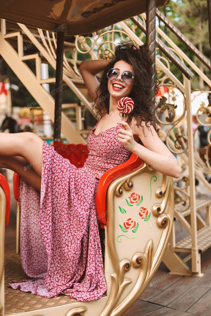 Happy lady in sunglasses and dress holding lolly pop candy riding on carousel in amusement park