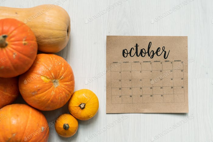 Overview of October calendar sheet and group of ripe orange and yellow pumpkins