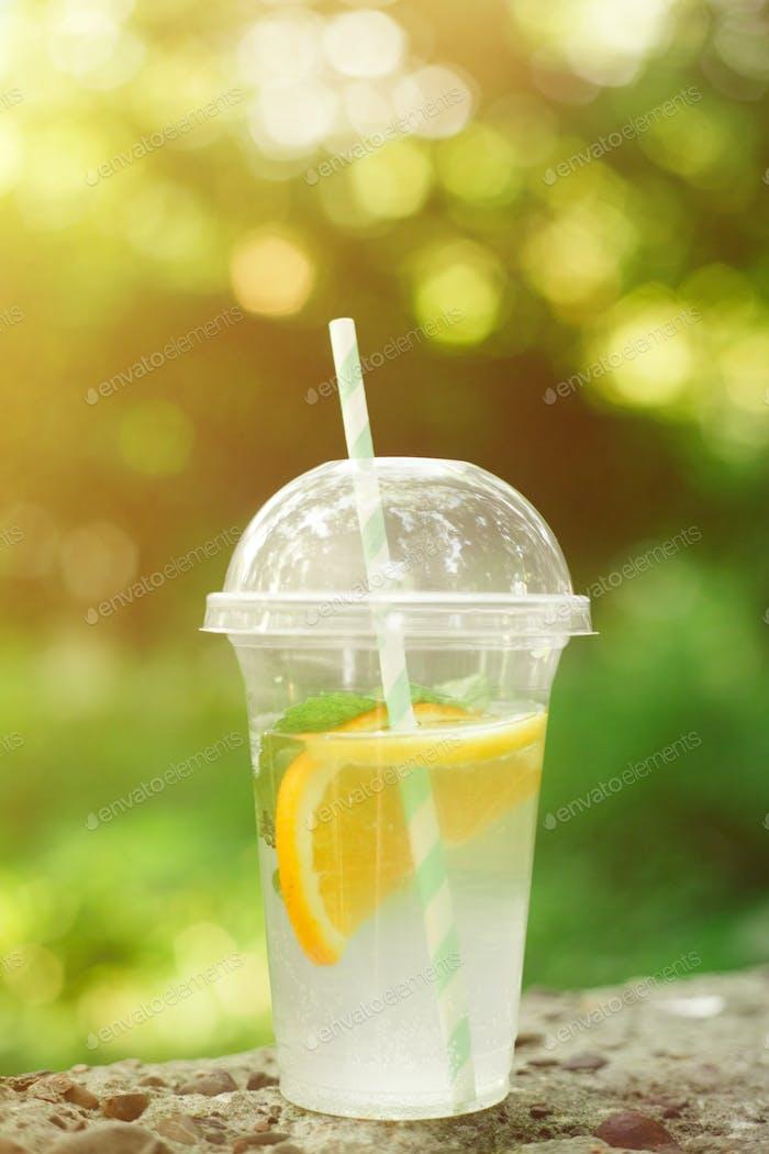 Bebida de verano Limonada fresca con naranja y menta en la taza de plástico