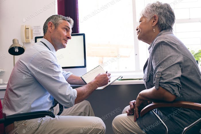Caucasian doctor prescribing medicine to senior African American woman in clinic at retirement home