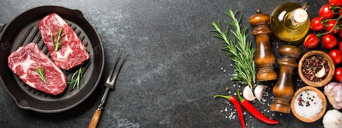 Frische rohe Rib Eye Steaks auf Grillpfanne und Gewürze auf schwarzem Steintisch