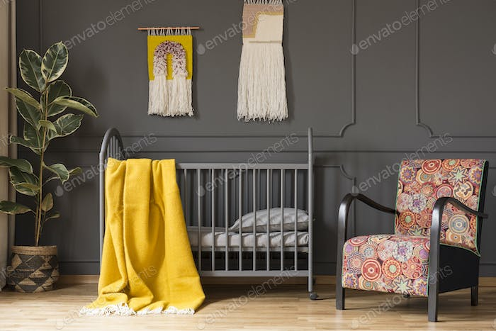 Patterned armchair next to bed with yellow blanket in kid's bedr